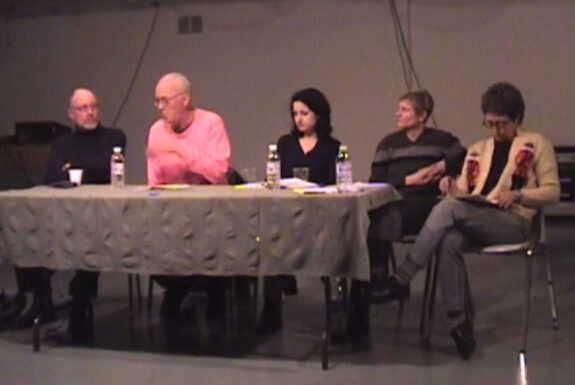 Panelists Bruce Barber, Clive Robertson, Alissa Firth-Eagland, Tangy Duff and moderator Johanna Householder sit at a long table conversing as part of the panel Images versus Iconoclasms or shooting sacred cows from a train of thought, 2002