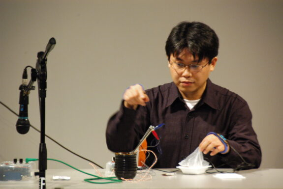 Adachi Tomomi performing Japanese Sound Poetry Improvisation Electric Chopsticks & Cup at XPACE Cultural Centre